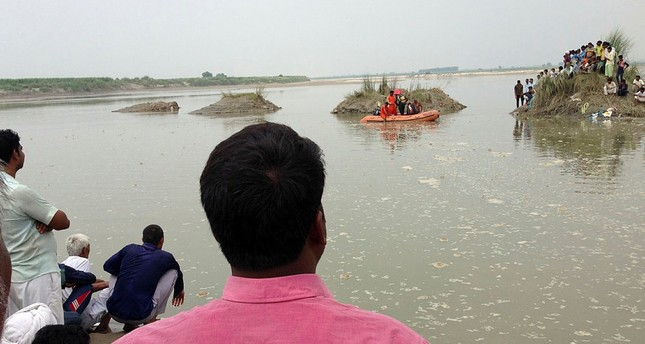 Villagers gather at the spot of a boat capsize as rescuers search in the Yamuna River near Baghpat town in Uttar Pradesh state, India, Thursday, Sept.14, 2017. (AP Photo)