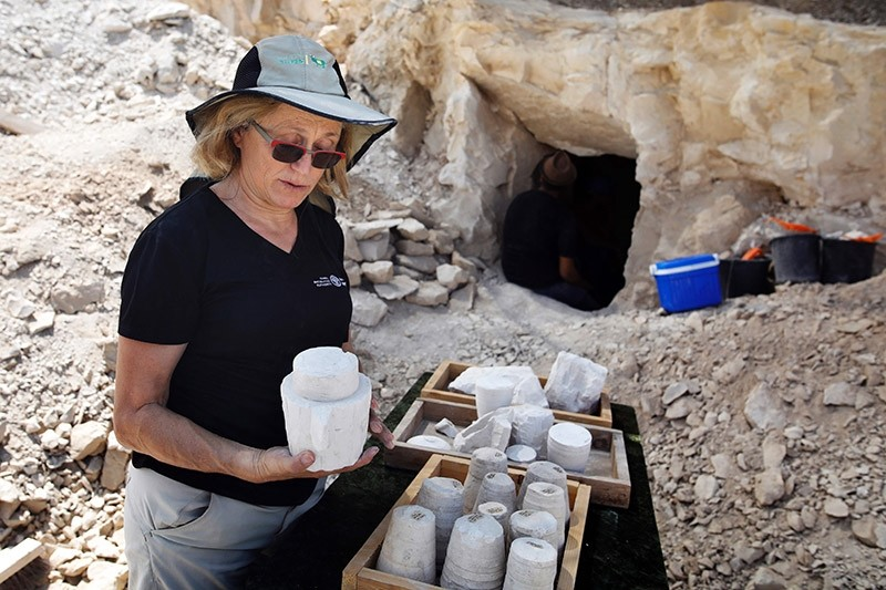Yardena Alexander, an Israeli archeologist, inspects chalkstone cores and mugs uncovered two-months prior at an excavation site dating to the Roman period in the Israeli village of Reina (AFP Photo)