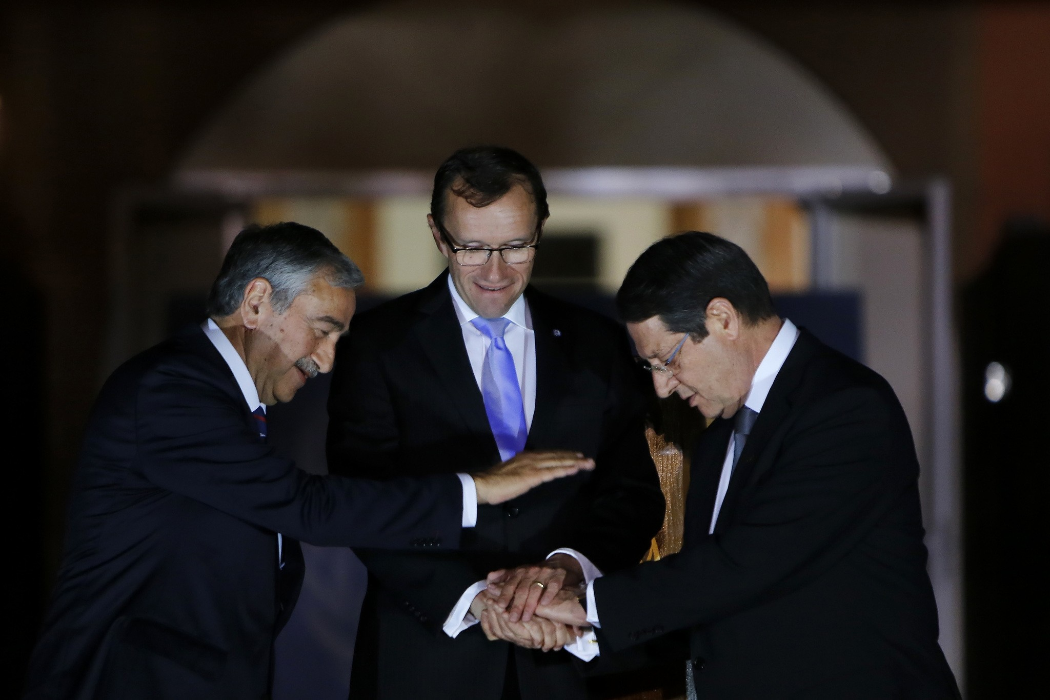 Cyprus' president Nicos Anastasiades, right, Turkish Cypriot leader Mustafa Akinci, left, and United Nations envoy Espen Barth Eide shake hands after a dinner at the Ledra Palace Hotel inside the UN controlled buffer zone. (AP Photo)