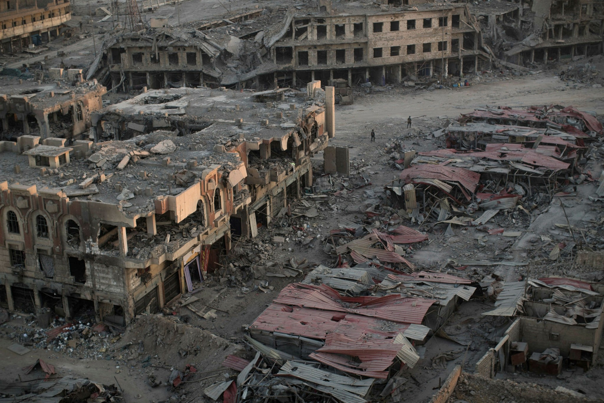 People walk through a damaged neighborhood as the sun sets on the west side of Mosul, Iraq on July 11.