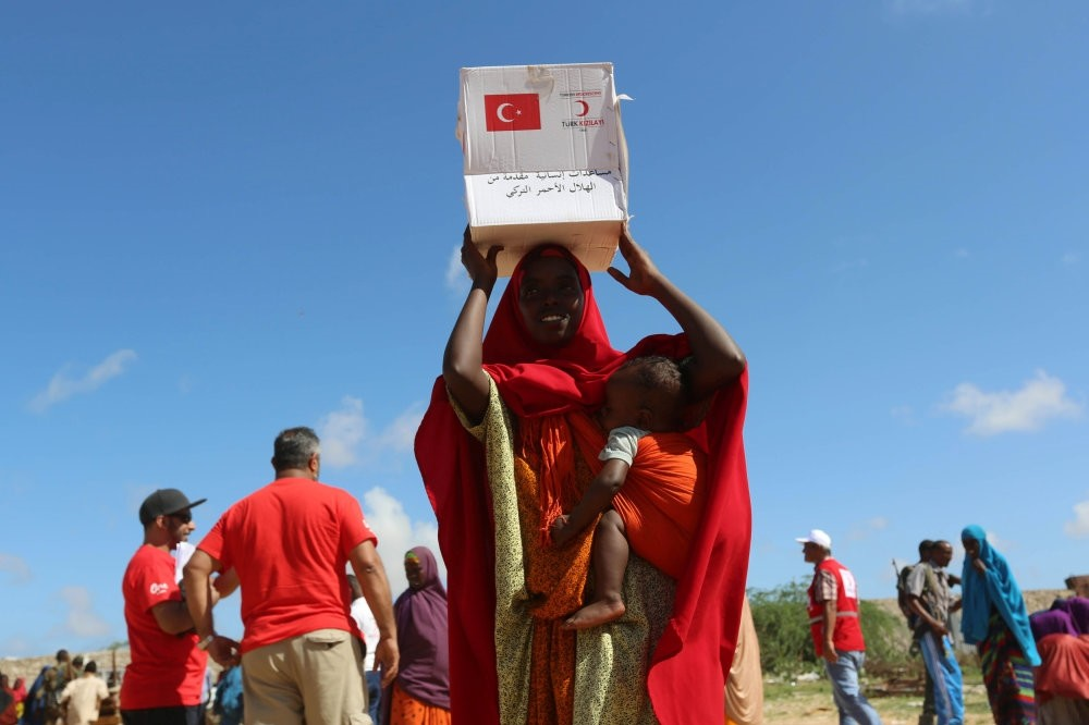 A displaced Somali woman carries a box of food distributed by the Turkish Red Crescent in Mogadishu on May 23.