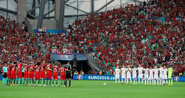 Poland's and Portugal's players line up during a moment of applause in memory of victims of the Istanbulairport attack prior to the Euro 2016 quarter-final football match between Poland and Portugal. AFP Photo