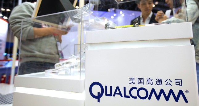 Visitors look at a display booth for Qualcomm at the Global Mobile Internet Conference in Beijing.