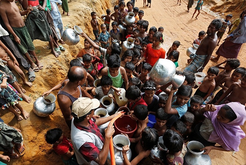 Rohingya refugee kids struggle to fill their empty containers with drinking water at Kutupalong refugee camp near Cox's Bazar, Bangladesh November 5, 2017. (Reuters Photo)