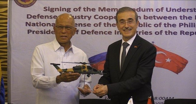 Defense Industries President İsmail Demir, right, presented Filipino Defense Secretary Delfin Lorenzana, left, with a model of the T129 ATAK helicopter  during the signing ceremony  of a memorandum of understanding, Manila, yesterday.