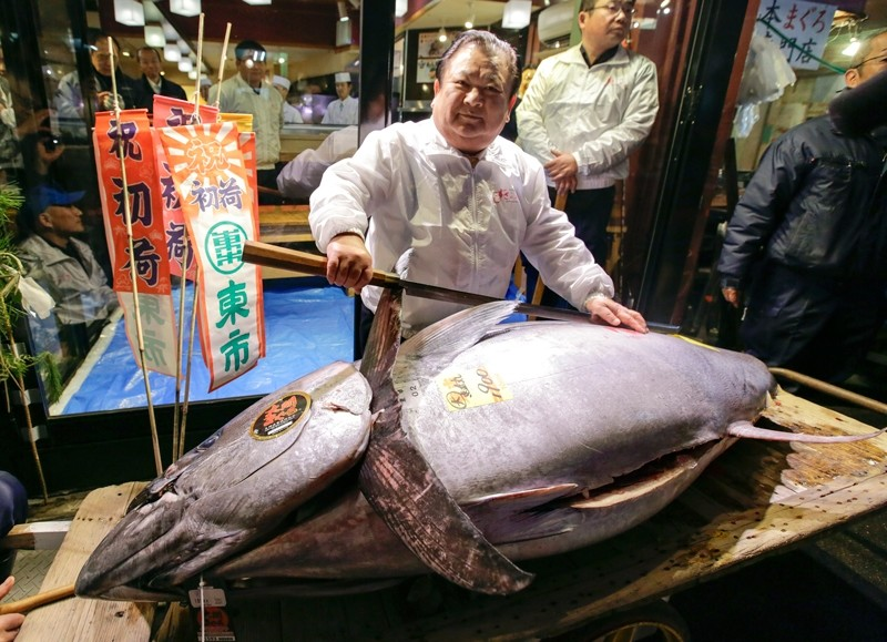 Kiyoshi Kimura (C), who runs the Sushi Zanmai chain sushi restaurant, poses with a tuna cutting knife in front of his the bluefin tuna he bid on in the final year-opening auction at Tsukiji Market in Tokyo, Japan, 05 January 2018 (EPA Photo)