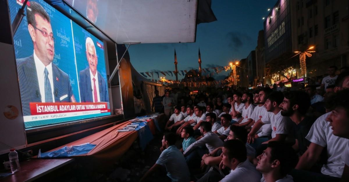 Spectators watch the live debate between the two major metropolitan municipality candidates in Istanbul's Esenler district, June 17, 2019.
