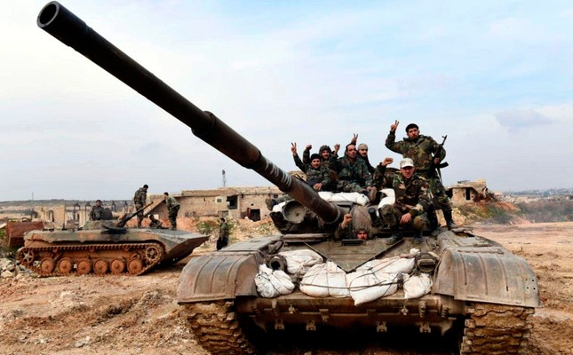 This Monday, Jan. 27, 2020, photo, released by the Syrian official news agency SANA, Syrian regime soldiers flash the victory sign as they stand on their tank in western rural Aleppo, Syria. SANA via AP