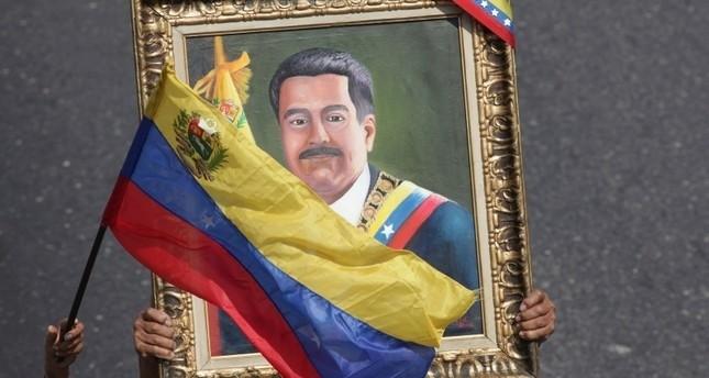 مؤيدون لمادورو يرفعون لوحة له خلال إحدى المسيرات بالعاصمة الفنزويلية كاراكاس 1 مايو 2019  (أسوشيتد برس)