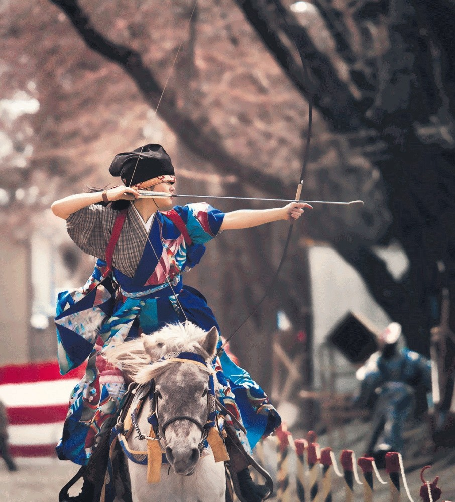 Aiming at three wooden targets, Japanese archers try to hit them with their turnip-headed arrows using yumi bows.