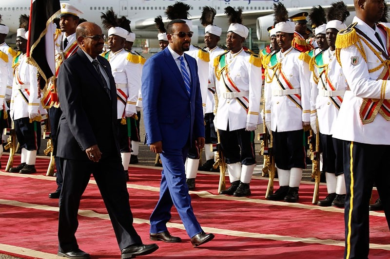 Ethiopian Prime Minister Abiy Ahmed (2R) reviews the honour guard with Sudanese President Omar al-Bashir (L) following his arrival in Khartoum for an official visit to Sudan on May 2, 2018. (AFP Photo)