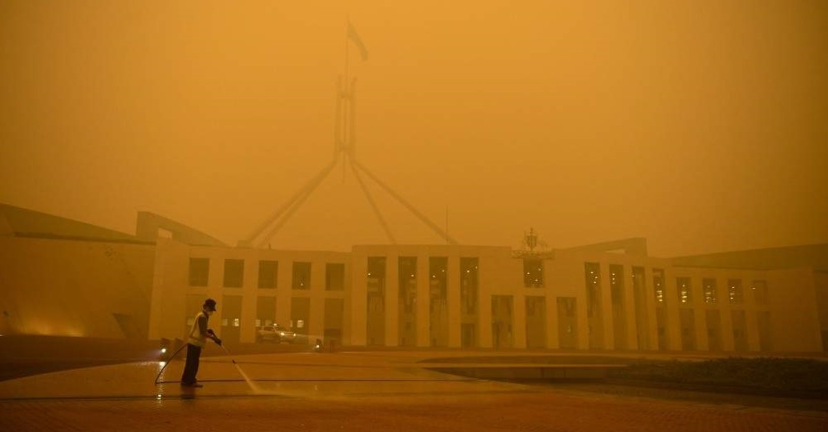 A man cleans the forecourt of Parliament House surrounded by smoke haze early morning in Canberra, Sunday, Jan. 5, 2020. (AP Photo)