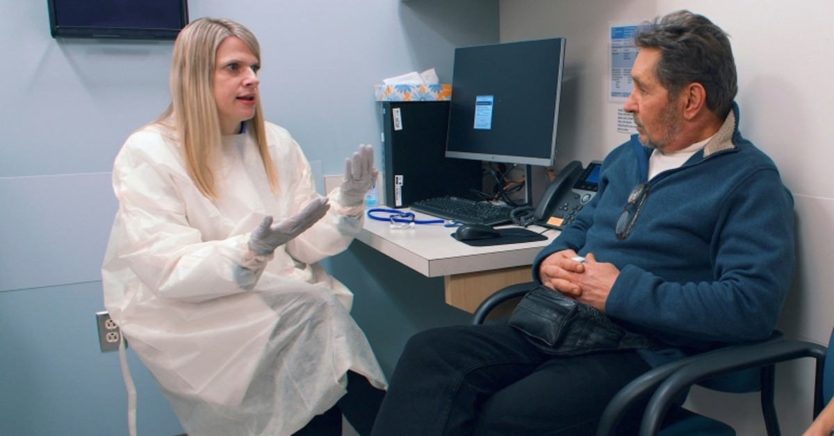 In this February 2019 photo provided by Brigham and Women's Hospital, Dr. Ann Woolley, an infectious disease specialist, speaks with patient Mark Natichinoi at the hospital in Boston. (AP Photo)