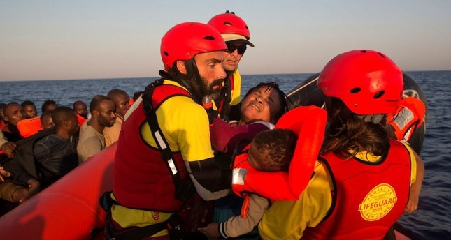 A woman from Nigeria and her baby are helped by members of the Proactiva Open Arms NGO, before transferring them to an Italian navy ship.