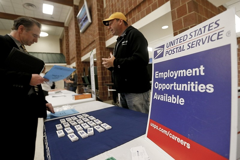a recruiter from the postal service, right, speaks with an attendee of a job fair in Cheswick, Pa. (AP Photo)