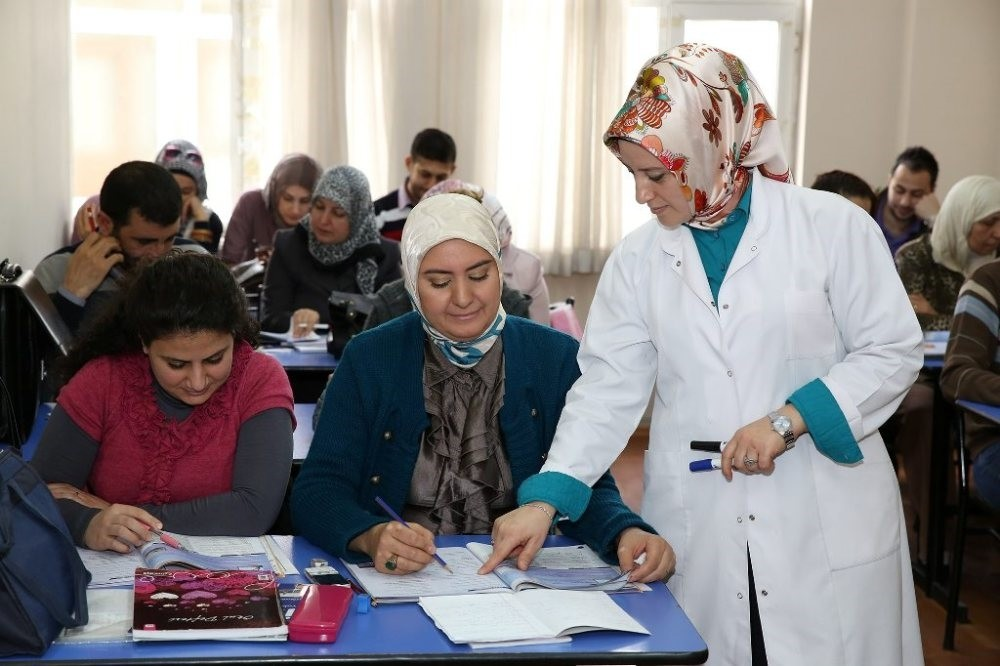 A teacher helps Wafa Mourad, a Syrian woman, in a Turkish class run by a local municipality in Istanbul.