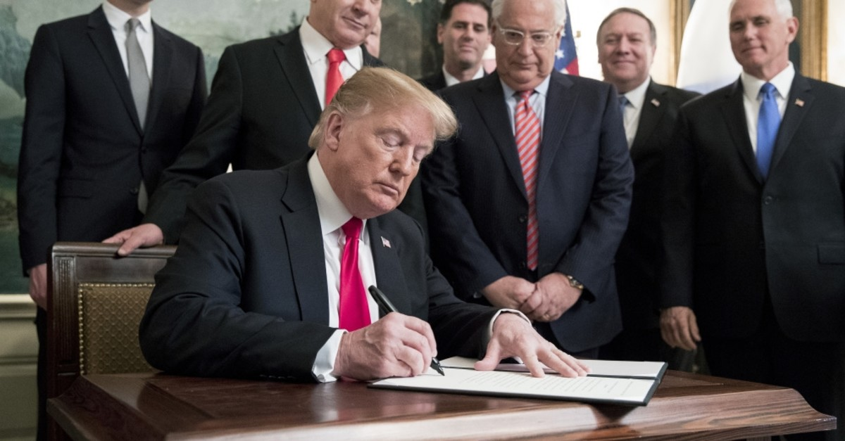 U.S. President Donald Trump (C) signs an order recognizing the Golan Heights as Israeli territory, in front of Prime Minister of Israel Benjamin Netanyahu (back C), in the Diplomatic Reception Room of the White House in Washington, March 2, 2019.