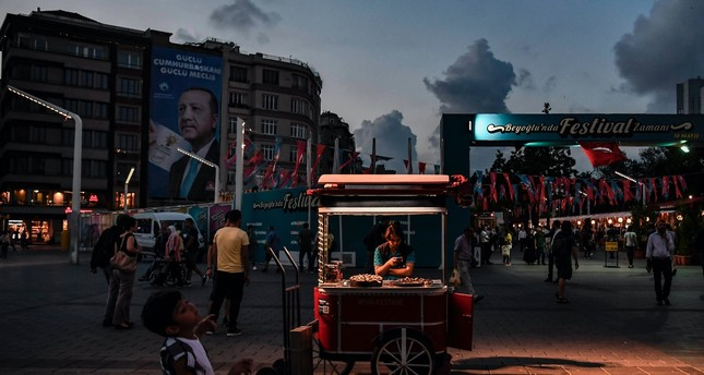 A man sells chestnuts in Taksim Square as a campaign poster for President Recep Tayyip Erdoğan for the June 24, 2018 elections waves in the background, Istanbul, June 18, 2018.