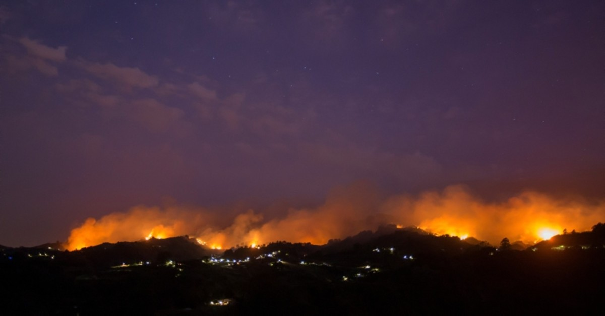 Flames and smoke from a forest fire are seen in the village of Moya, in the Canary Island of Gran Canaria, Spain, August 18, 2019. (Reuters Photo)
