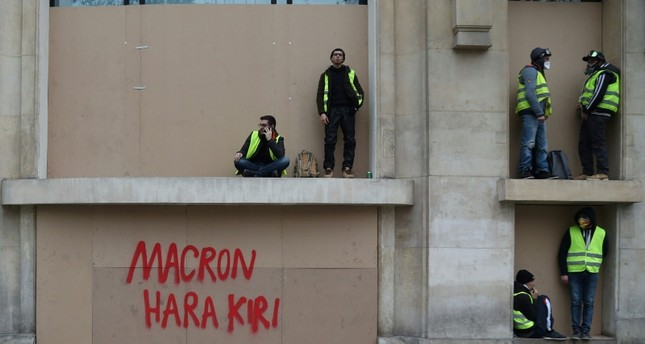 Protestors get some rest near an inscription reading Macron Hara Kiri during a demonstration of yellow vests (gilets jaunes) against rising costs of living they blame on high taxes in Paris, on December 8, 2018. (AFP Photo)