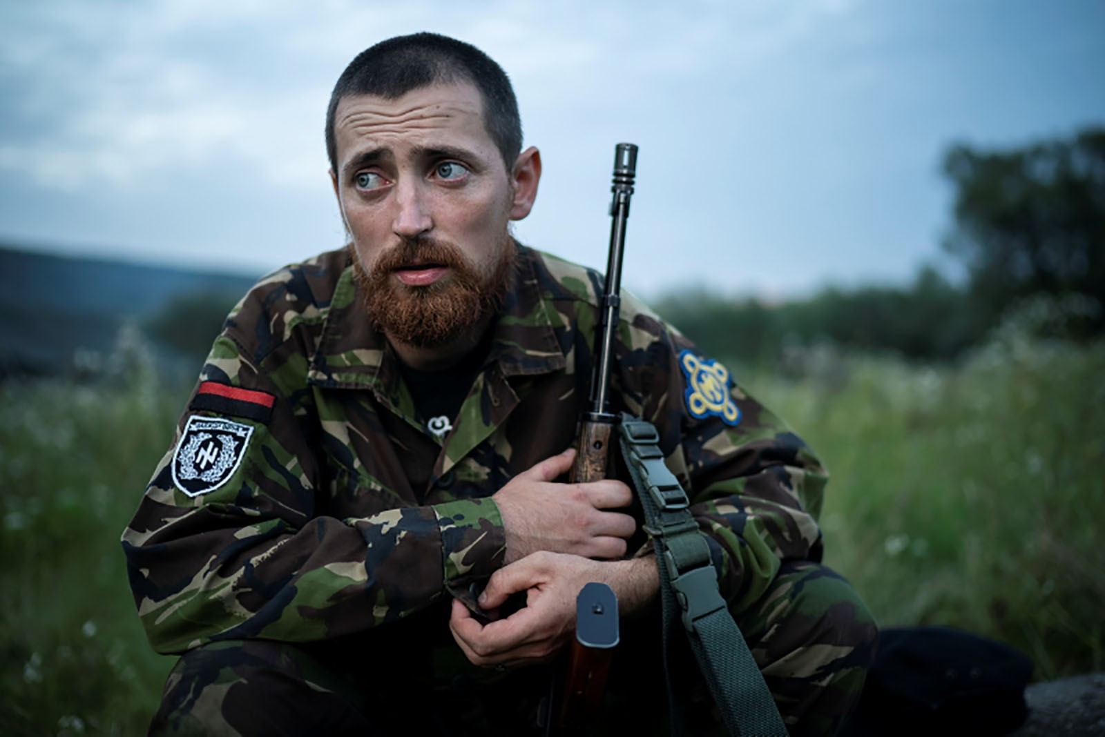 Yuri Chornota Cherkashin, head of Sokil Falcon, the youth wing of the nationalist Svoboda party, sits with his AK-47 rifle.