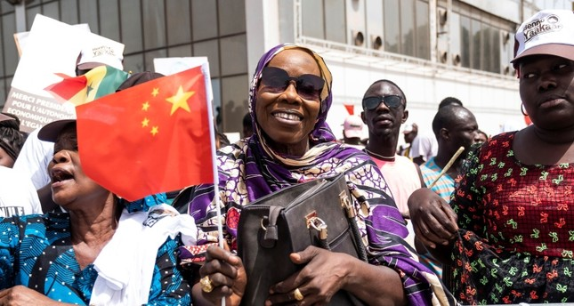 A Senegal resident welcomes Chinese President Xi Jinping in Dakar, Senegal, Saturday, July. 21, 2018. (AP Photo)