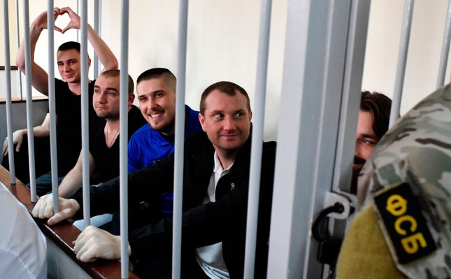 Ukrainian sailors sit inside a defendants' cage prior to a hearing at a court in Moscow on July 17, 2019. (AFP Photo)