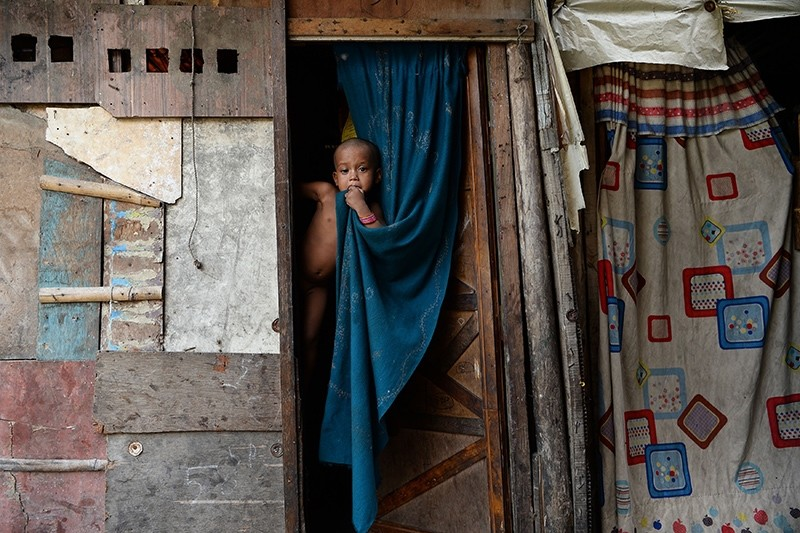 A young Rohingya refugee is held up in her makeshift shelter in New Delhi, India, Sept. 17, 2017. (AFP Photo)