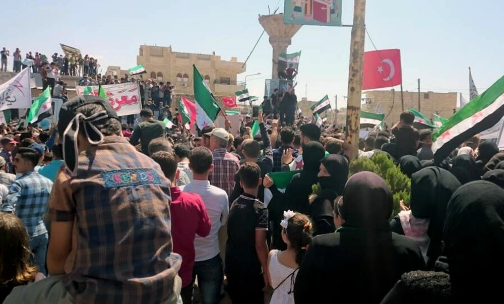 This image courtesy of Wissam Zarqa, a resident of Idlib, shows protesters holding Turkish flags and the flags of the Syrian revolution u0130Qin Idlib province, Syria, Friday.