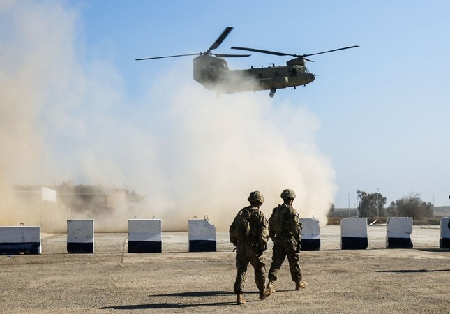 In this file photo taken on February 22, 2017, US troops walk as a US C-47 Chinook helicopter flies over the village of Oreij, south of Mosul. AFP Photo