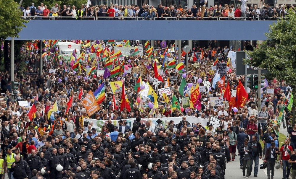 German riot police walk in front of protesters, including the terrorist PKK sympathizers, during demonstrations at the G20 Summit in Hamburg, July 8.
