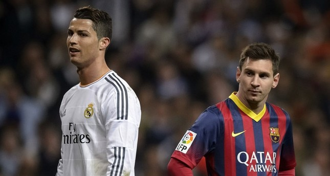 """Barcelona's Argentinian forward Lionel Messi (R) standing near Real Madrid's Portuguese forward Cristiano Ronaldo during a  """"El clasico"""" Spanish League football match."""