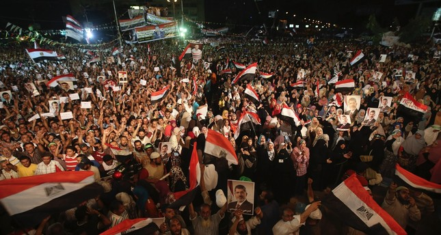 Supporters of Egypt's first democratically elected President Mohammed Morsi hold his portraits and wave flags in Cairo, July 10, 2013 a month before Egyptian military tanks ran over protestors in Tahrir square.