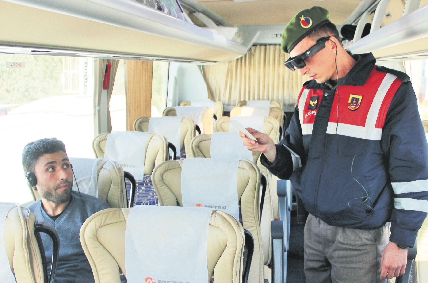 A gendarme checks the ID of a bus passenger with Takbul goggles.