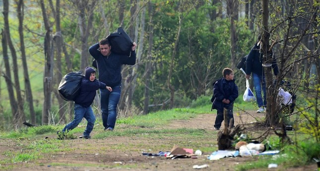A Syrian family carry their belongings through the forest near the Hungarian border fence at the Tompa border station transit zone on April 6. (AFP Photo)