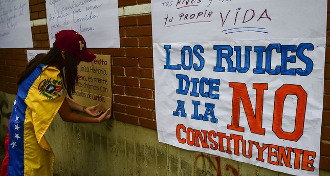 A woman wrapped in a Venezuelan national flag pastes a sign against President Maduro and his call for Constituent Assembly on the wall of a school which will be used as polling station, in Caracas, on July 24, 2017. (AFP Photo)
