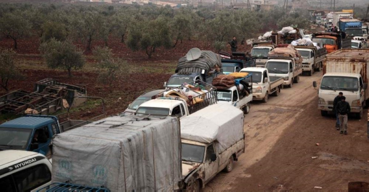 Syrians fleeing towns and villages in the countryside of the northern province of Aleppo drive through the town of Ghazaouia on January 18, 2020. (AFP Photo)