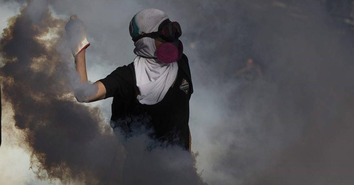 A demonstrator throws a tear gas canister back at riot police during a protest against Chilean President Sebastian Pinera's government in Santiago, on Dec. 27, 2019. ( AFP Photo)