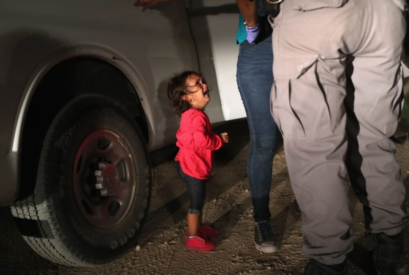 A two-year-old Honduran asylum seeker cries as her mother is searched and detained near the U.S.-Mexico border on June 12, 2018 in McAllen, Texas. (AFP Photo)