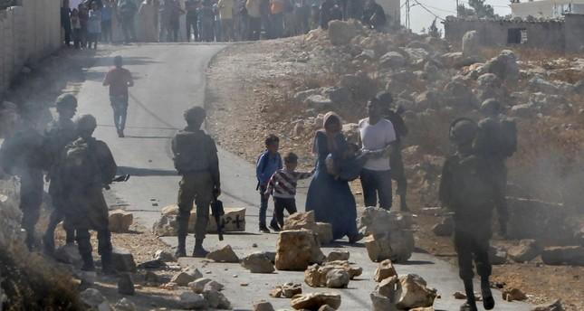 Palestinians evacuate an injured person as protesters clash with Israeli troops near Caisan, southeast of Bethlehem, where Israeli bulldozers demolished houses that were reportedly built without a license, on Oct. 10, 2019. (AFP Photo)
