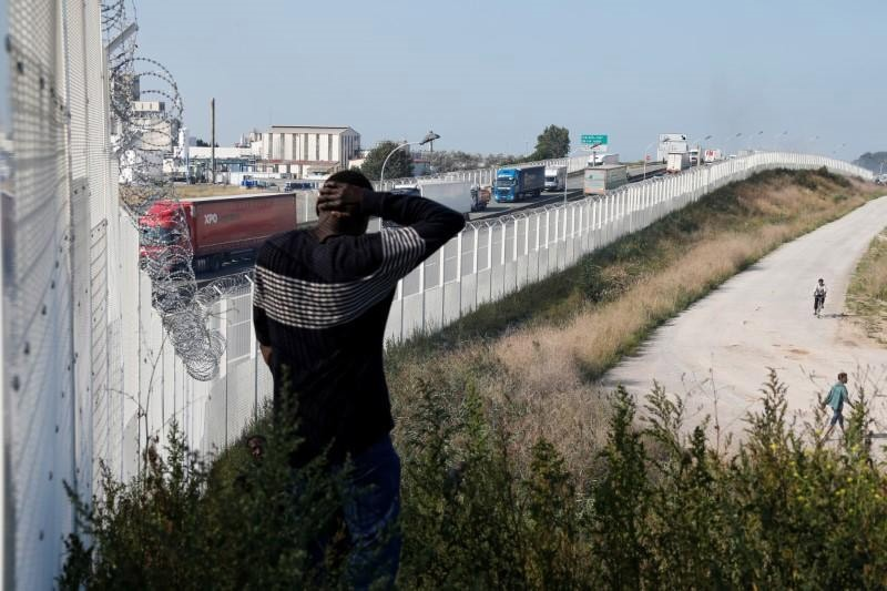 Migrant walks past the fence which secures the approach to the city from migrants trying to reach Britain, in Calais, France, September 21, 2016. (Reuters Photo)