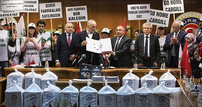 Union representatives deliver sugar sacks containing signatures against privatization of sugar factories to Confederation of Turkish Trade Unions (Türk-İş) Chairman Ergün Atalay in a ceremony in Ankara, March 27, 2018. (AA Photo)