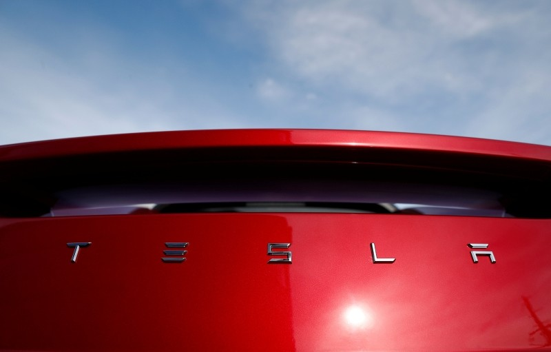In this April 15, 2018, file photo the sun shines off the rear deck of a roadster on a Tesla dealer's lot in the south Denver suburb of Littleton, Colo. (AP Photo)