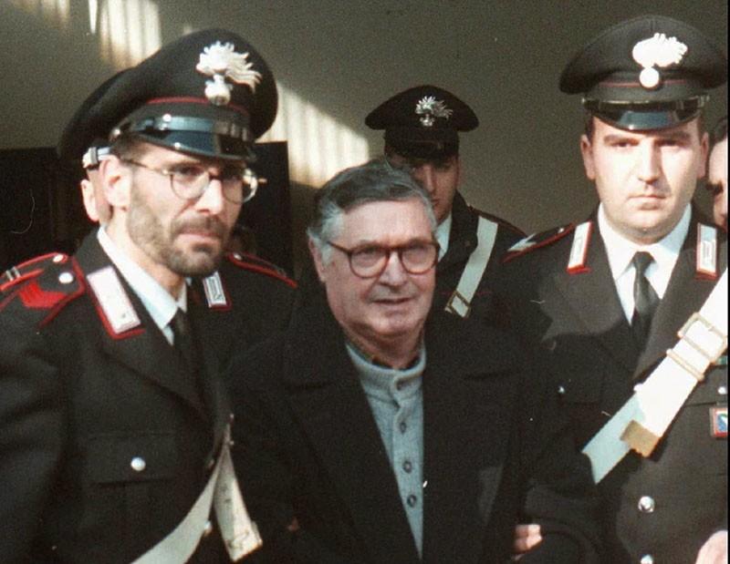 In this Jan. 16, 1996 file photo, Mafia ''boss of bosses'' Salvatore ''Toto'' Riina, center, enters handcuffed into Bologna's bunker-courtroom, escorted by Carabinieri, Italian paramiliary police, in Bologna, Italy (AP Photo)