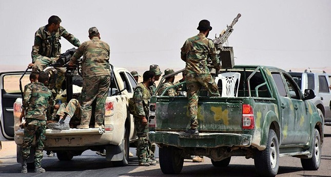 This file photo released, Sept. 4, 2017 by the Syrian official news agency SANA, shows Assad regime troops and pro-regime gunmen standing on pickup trucks mounted with heavy machine-guns, in the eastern city of Deir el-Zour, Syria. (via AP)