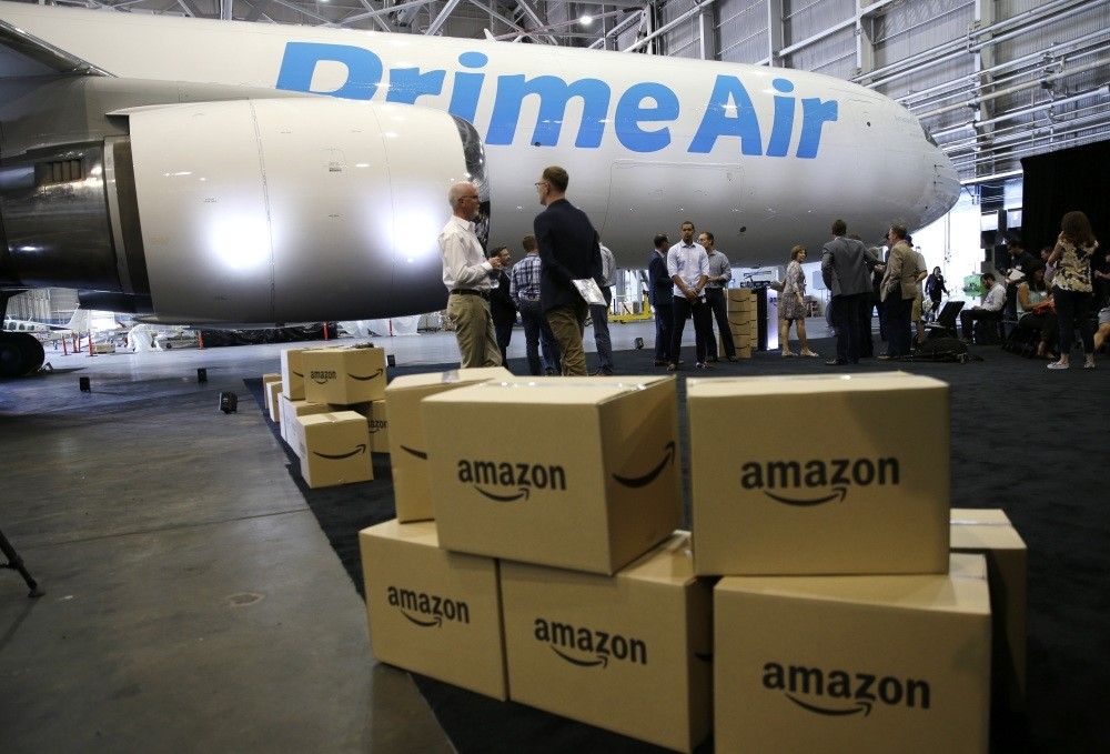 Amazon.com boxes are stacked near a Boeing 767 Amazon Prime Air cargo plane on display in a Boeing hangar.