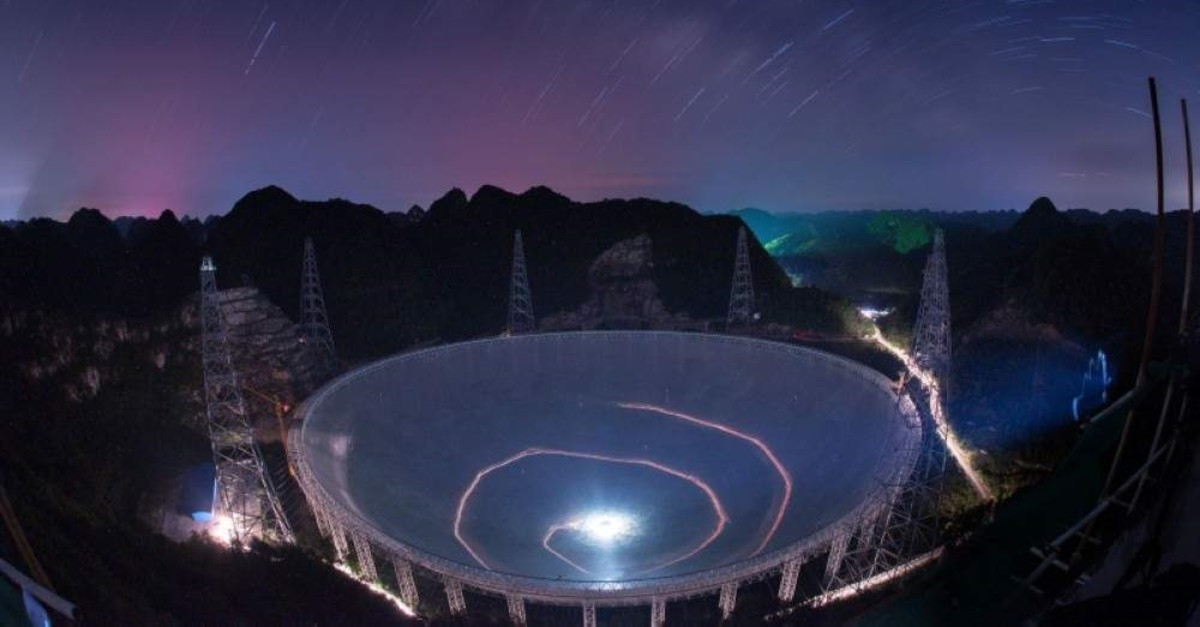 In this photo released by China's Xinhua News Agency, a vehicle leaves light trails in a long exposure photo as it drives near the 500-meter-wide Aperture Spherical Telescope (FAST) in Pingtang County in southwestern China's Guizhou Province, June 27, 2016. (AP Photo)