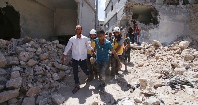 Members of the Syrian Civil Defence (White Helmets) and civilians carry a wounded man following a reported regime airstrike in the southern outskirts of Idlib province, July 12, 2019.