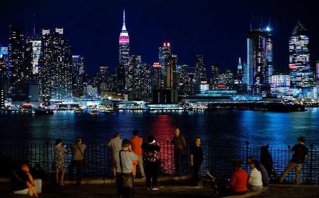 People look at the New York skyline with the Empire State Building lit in burgundy and white in honor of Qatar Airways and its 10th Anniversary of flying to the United States, as seen from Weehawken, New Jersey on June 27, 2017. (AFP Photo)