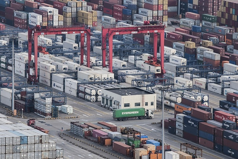 A cargo truck drives amid stacked shipping containers at the Yangshan port in Shanghai, Thursday, March 29, 2018. (AP Photo)